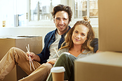Buy stock photo Shot of an affectionate young couple eating takeout while surrounded by boxes