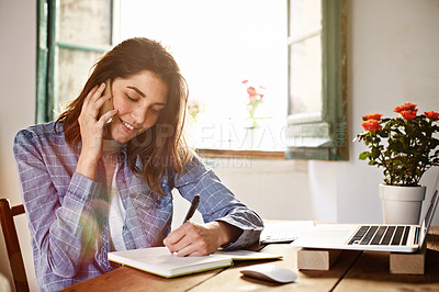 Buy stock photo Shot of an attractive young woman sitting by a window at home talking on a cellphone and writing on a notepad