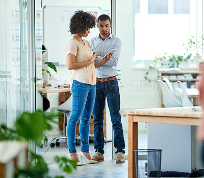 Buy stock photo Shot of two office colleagues having a discussion over a digital tablet