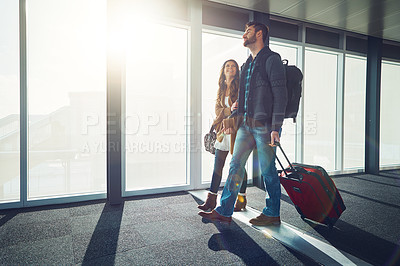 Buy stock photo Shot of a young couple walking together in an airport with their luggage while holding one another