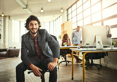 Buy stock photo Cropped portrait of a handsome young businessman sitting in the office with his colleagues in the background