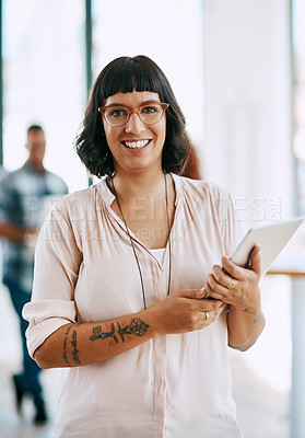 Buy stock photo Portrait of a young woman holding a digital tablet in a modern office with her colleagues in the background