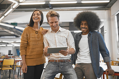 Buy stock photo Cropped shot of three young businesspeople looking at a tablet in their office