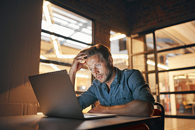 Buy stock photo Shot of a handsome young man looking thoughtful while working late in his office