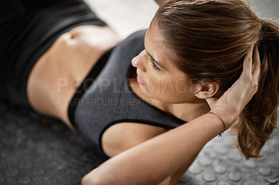 Buy stock photo Shot of a young woman doing sit-ups at the gym