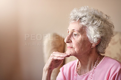 Buy stock photo Shot of a senior woman sitting on a chair and looking thoughtful at home