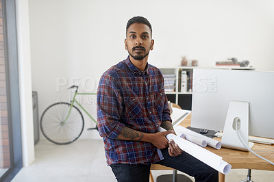 Buy stock photo Portrait of a creative young architect posing with a roll of blueprints in his office