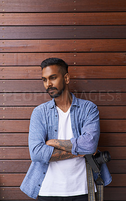 Buy stock photo Shot of a handsome young man posing against a brown background outside