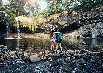 Buy stock photo Rearview shot of two young women embracing each other looking at a waterfall in the forest