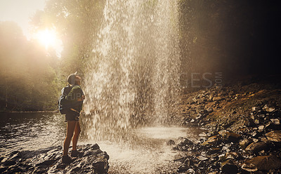 Buy stock photo Shot of a young woman eyes closed enjoying the water from a waterfall in nature