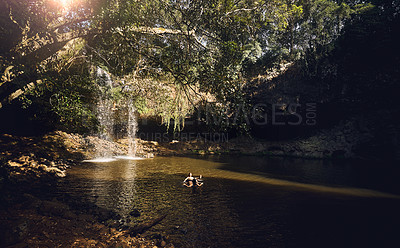 Buy stock photo Shot of two young female best friends enjoying the water by a waterfall in nature