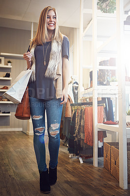 Buy stock photo Shot of a young woman walking though a boutique with a shopping bag