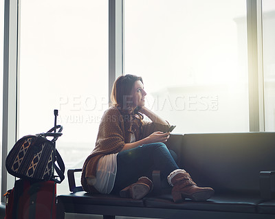 Buy stock photo Shot of a young woman sitting in an airport with her luggage and holding her cellphone while looking outside