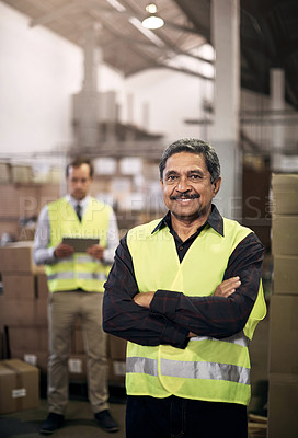 Buy stock photo Portrait of a mature man standing in a factory with his colleague in the background