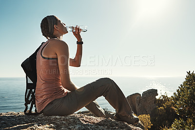 Buy stock photo Shot of a young woman drinking water while out on a hike through the mountains