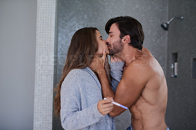 Buy stock photo Shot of a happy young couple kissing after taking a pregnancy test at home