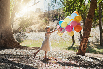 Buy stock photo Shot of a little girl playing with a bunch of balloons outside