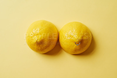 Buy stock photo Studio shot of two lemons with a ring piercing against a yellow background