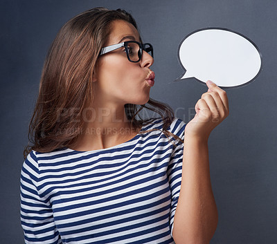 Buy stock photo Studio shot of an attractive young woman holding a blank speech bubble against a gray background