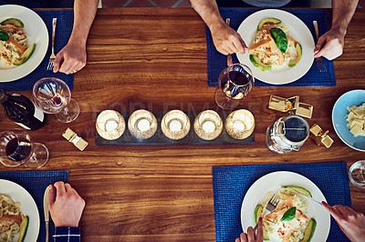 Buy stock photo Shot of a group of unrecognizable people enjoying a meal at the dining room table at home