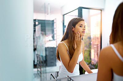 Buy stock photo Shot of an attractive young woman touching her skin while looking in the bathroom mirror