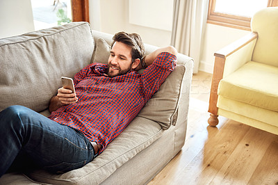 Buy stock photo Shot of a relaxed young man using a mobile phone on the sofa at home