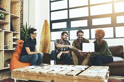 Buy stock photo Shot of a group of designers using a laptop in their brainstorming session