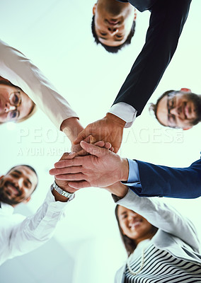 Buy stock photo Low angle shot of a diverse group of businesspeople joining their hands together in unity