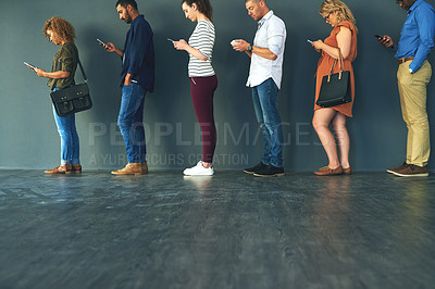 Buy stock photo Shot of a group of people standing in a row behind each other while using their phones
