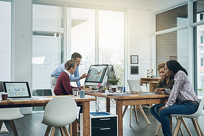 Buy stock photo Shot of a group of colleagues working together at their desks in a modern office