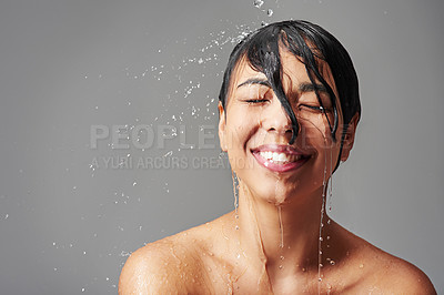 Buy stock photo Studio shot of a young woman enjoying a shower against a gray background