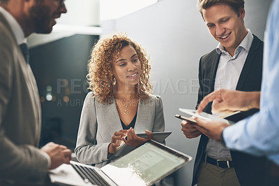 Buy stock photo Shot of a group of businesspeople using digital devices while brainstorming in an office