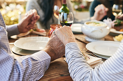 Buy stock photo Shot of two unrecognizable people holding hands at a dinner table outside