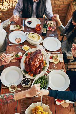 Buy stock photo High angle shot of a family saying grace at the dining table