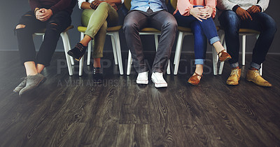 Buy stock photo Cropped studio shot of a group of people waiting in line on chairs against a gray background