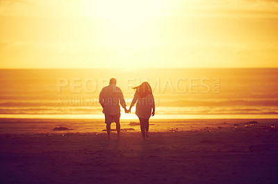 Buy stock photo Rearview shot of an affectionate mature couple walking hand in hand on the beach