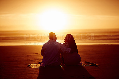 Buy stock photo Rearview shot of an affectionate mature couple enjoying the sunset while sitting on the beach