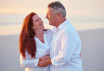 Buy stock photo Shot of mature people enjoying the sunset on the beach