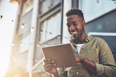 Buy stock photo Cropped shot of a handsome young man using his digital tablet outside