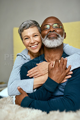 Buy stock photo Shot of a senior married couple embracing each other at home