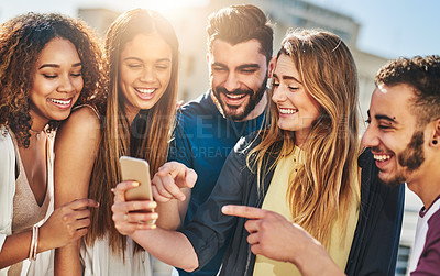 Buy stock photo Shot of young friends using a smartphone outside