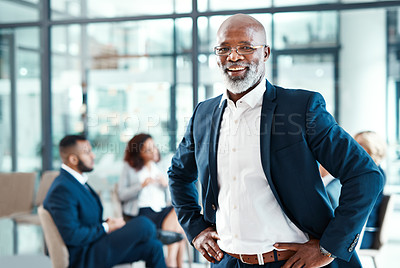 Buy stock photo Portrait of a confident mature businessman standing in a modern office with his colleagues in the background