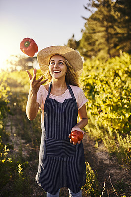 Buy stock photo Shot of a young woman juggling red peppers on a farm
