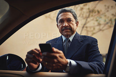 Buy stock photo Shot of a mature businessman using a phone while leaning against his car
