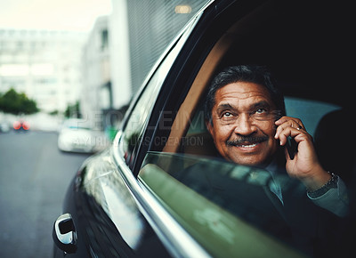 Buy stock photo Shot of a mature businessman using his phone while traveling in a car