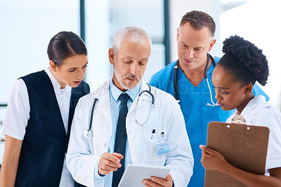 Buy stock photo Cropped shot of a group of medical professionals discussing something on a digital tablet