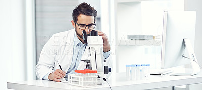 Buy stock photo Shot of a focused young male scientist making notes while looking trough a microscope and being seated inside a laboratory