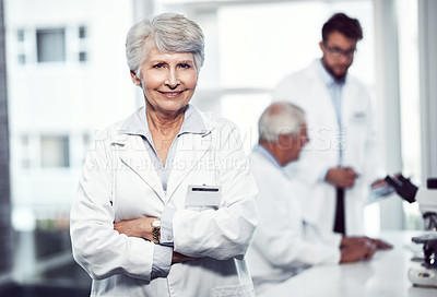 Buy stock photo Portrait of a cheerful elderly female scientist standing with arms folded and looking into the camera inside a laboratory
