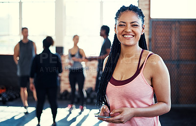 Buy stock photo Portrait of a cheerful young woman using her cellphone while looking into the camera before a workout in a gym