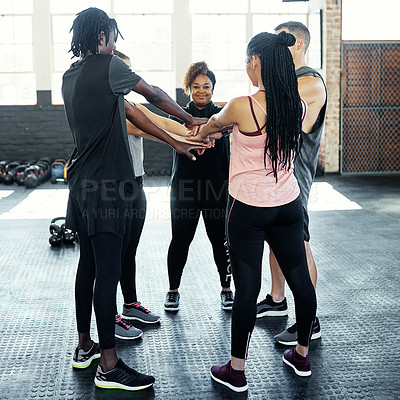 Buy stock photo Shot of a cheerful young group of people forming a huddle together while one looks at the camera before a workout session in a gym